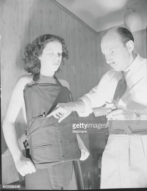 Captain Jacques Bril criminologist points to spent bullet lodged in the armored vest worn by his assistant
