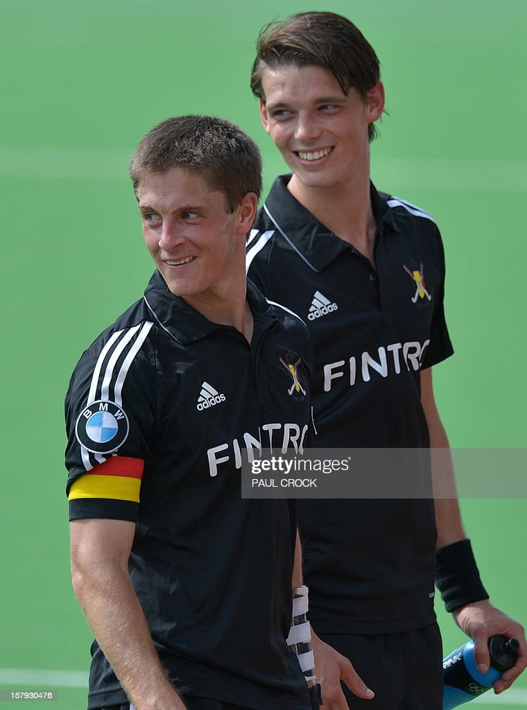 Captain Jerome Truyens of Belgium (L) and team-mate Felix Denayer (R) smile as they leave the pitch after their match against England at the men's Hockey Champions Trophy tournament in Melbourne on December 8, 2012. IMAGE STRICTLY RESTRICTED TO EDITORIAL USE - STRICTLY NO COMMERCIAL USE AFP PHOTO / Paul CROCK