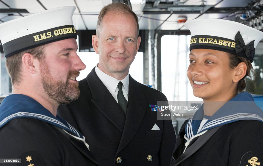 Captain Jerry Kyd (C) is pictured with LA (Leading Airman) Thomas Hardcastle (L), and LPT (Leading Physical Trainer) Michelle Mattinson as he takes over as the first seagoing Captain of the Royal Navy's new aircraft carrier HMS Queen Elizabeth on May 24, 2016 in Rosyth, United Kingdom. The Captain will lead men and women who will operate the 65,000 tonne flagship aircraft carrier for the Royal Navy. She is expected to be in commission from 2017.