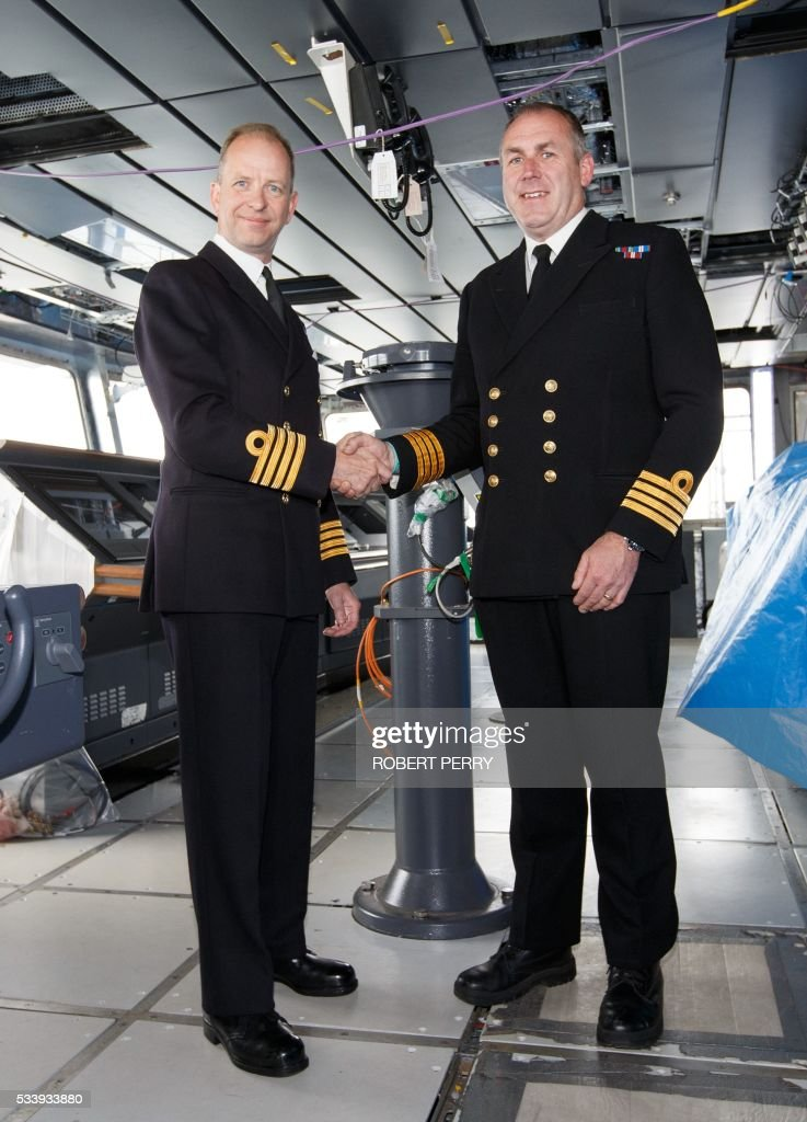 Captain Jerry Kyd (L), the new first Commanding Officer of British aircraft carrier HMS Queen Elizabeth shakes hands with current Senior Naval Officer, captain Simon Petitt (R) who has been Senior Naval Officer of HMS Queen Elizabeth on the bridge of the 65,000-tonne ship in Rosyth dockyard in Scotland, on May 24, 2016. / AFP / Robert Perry