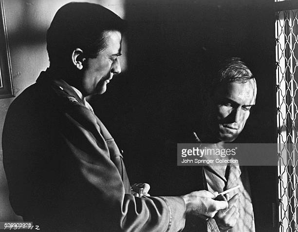 Captain Josiah Newman offers a cigarette to Captain Paul Cabot Winston one of his patients at the psychiatric ward of the US veterans hospital during...
