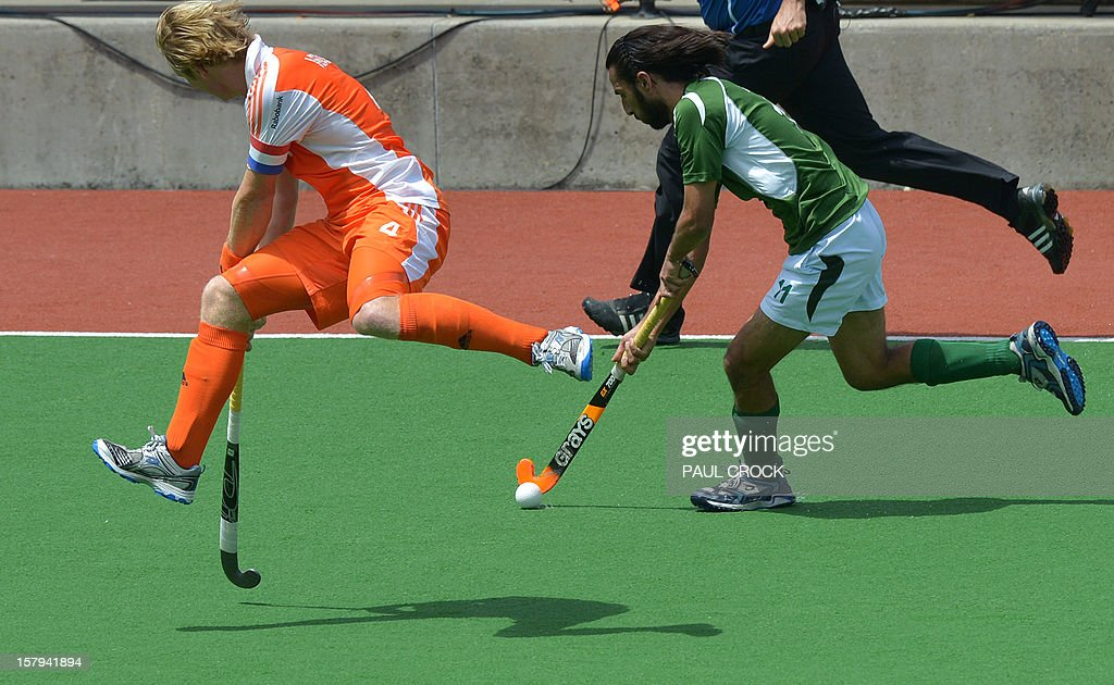 Captain Klaas Vermeulen of The Netherlands (L) leaps as Shakeel Abbasi of Pakistan makes a pass during their semi final match at the men's Hockey Champions Trophy in Melbourne on December 8, 2012. IMAGE STRICTLY RESTRICTED TO EDITORIAL USE - STRICTLY NO COMMERCIAL USE AFP PHOTO / Paul CROCK