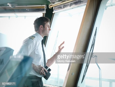 Captain looking out of window on ships bridge