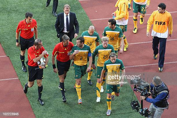 Captain Lucas Neill of Australia talks with Referee Roberto Rosetti as the teams go off at half time during the 2010 FIFA World Cup South Africa...