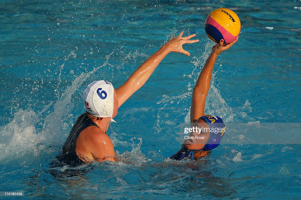 Captain Marina Canetti of Brazil looks to pass the ball under pressure from captain Orsolya Takacs of Hungary during the Women's Water Polo first preliminary round match between Hungary and Brazil during Day Two of the 15th FINA World Championships at Piscines Bernat Picornell on July 21, 2013 in Barcelona, Spain.