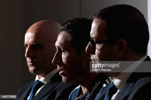Captain Mark Milligan speaks to the media as coach Kevin Muscat and chairman Anthony Di Pietro look on during a Melbourne Victory ALeague media...