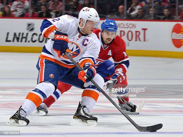 Captain Mark Streit of the New York Islanders keeps the puck away from Tomas Plekanec of the Montreal Canadiens during the NHL game on December 13...