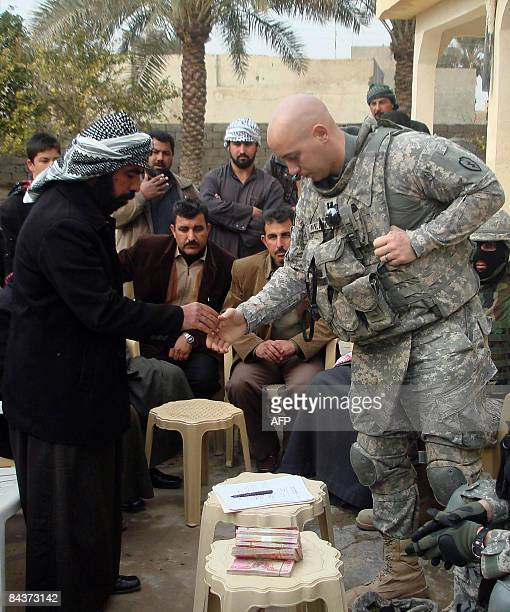 US Captain Michael Pavlisak of Bravo company 2nd battalion 35th lnfantry regiment shakes hands with the elder brother of two Iraqi men killed...