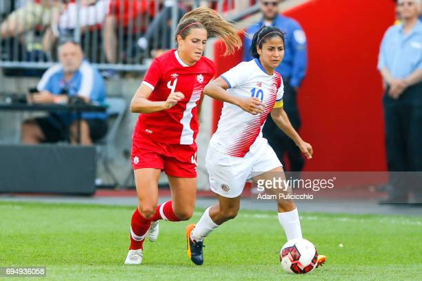 Captain Midfielder Shirley Cruz of Team Costa Rica moves the ball as Defender Shelina Zadorsky of Team Canada applies pressure from behind in a...