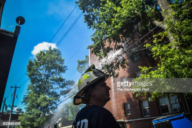 Captain Mike White watches and directs his firefighters at the scene of a large fire at 1300 block of Peabody Street NW that displaced more than 100...