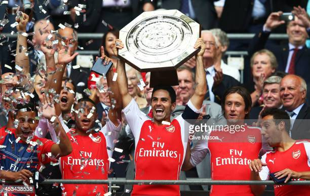 Captain Mikel Arteta of Arsenal holds up the trophy alongside teammates Alex OxladeChamberlain Tomas Rosicky and Santi Cazorla after winning the FA...