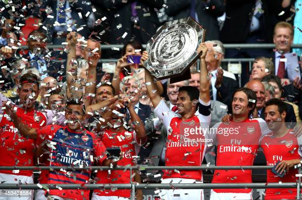 Captain Mikel Arteta of Arsenal holds up the trophy alongside teammates Tomas Rosicky and Santi Cazorla after winning the FA Community Shield match...