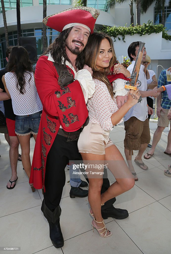 Captain Morgan and Sports Illustrated Cover Model Chrissy Teigen pose during the Captain Morgan White Rum and Sports Illustrated Swimsuit's 50th anniversary poolside celebration at Fontainebleau Miami Beach on February 19, 2014 in Miami Beach, Florida.