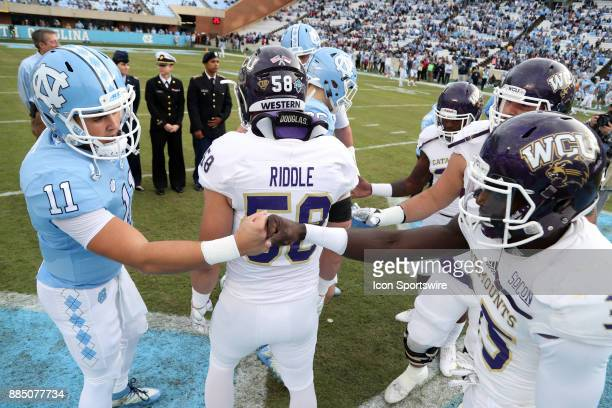 UNC captain Nathan Elliott and WCU captain Keion Crossen bump fists after the coin toss during the North Carolina Tar Heels game versus the Western...