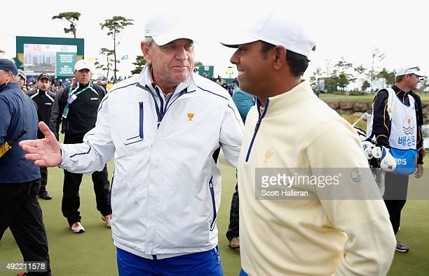 Captain Nick Price chats with Anirban Lahiri of India and the International Team after the Sunday singles matches at The Presidents Cup at Jack...