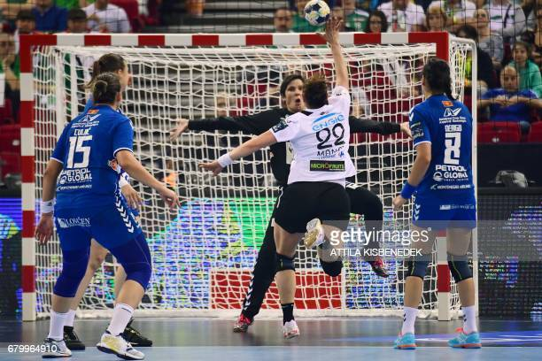 Captain Oana Manea of Romanian CSM Bucaresti scores a goal against goalkeeper Darly de Paula of Montenegrian Budocnost between Dragana Cvijic and...