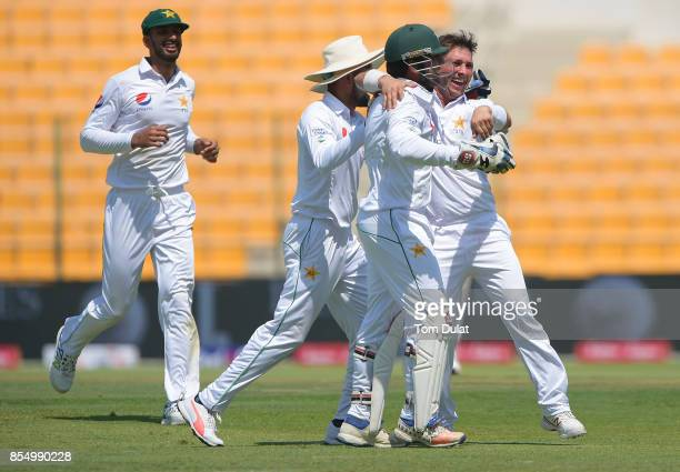 Captain of Pakistan Sarfraz Ahmed celebrates with Yasir Shah taking the wicket of Kusal Mendis of Sri Lanka during Day One of the First Test between...