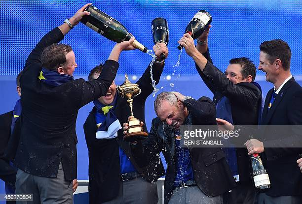 Captain of Team Europe Paul McGinley of Ireland is sprayed with champagne as he holds the trophy after his team retained the Ryder Cup on the final...