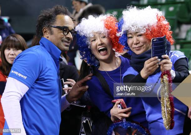 Captain of Team France Yannick Noah poses with fans after winning the doubles match and the tie 30 on day 2 of the Davis Cup World Group first round...