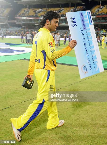 Captain of the Chennai Super Kings Mahendra Singh Dhoni holds the runners up cheque as he walks out after the IPL Twenty20 cricket final match...