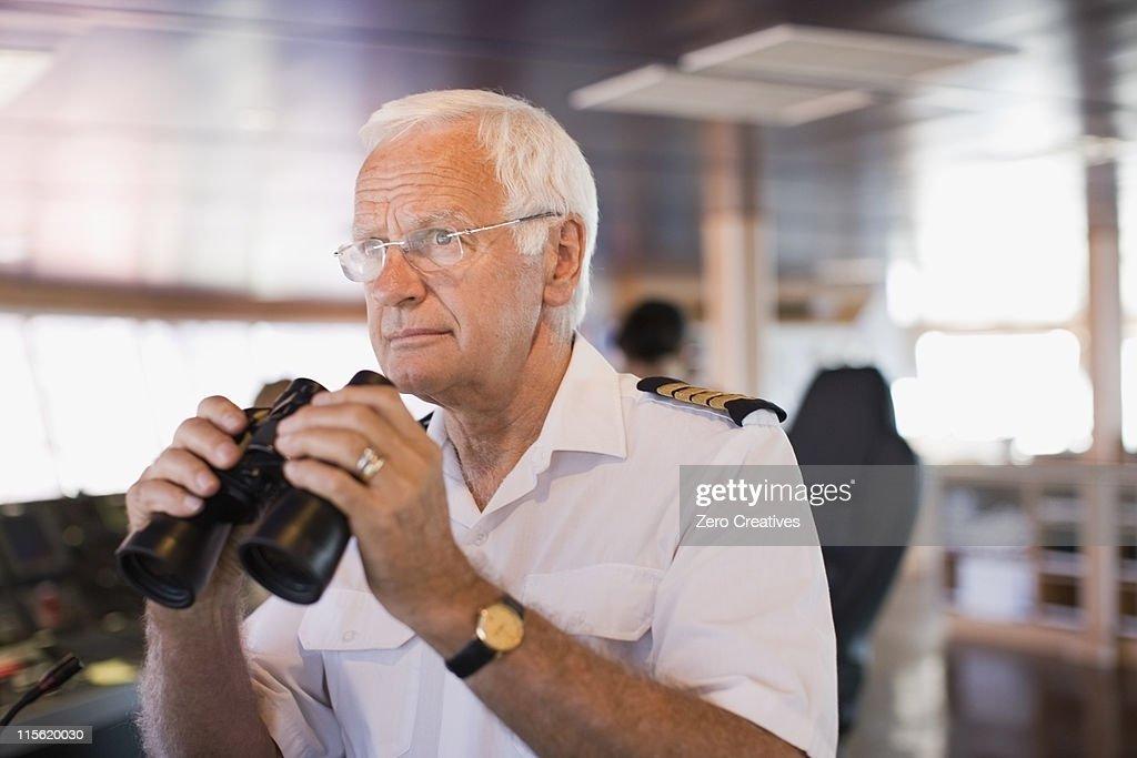 Captain on ship holding  a telescope