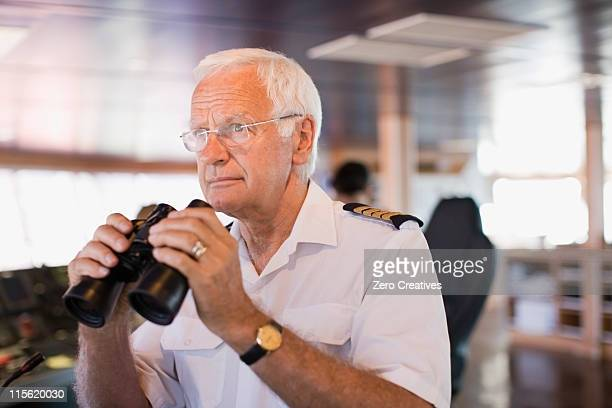 Captain on ship holding  a telescope