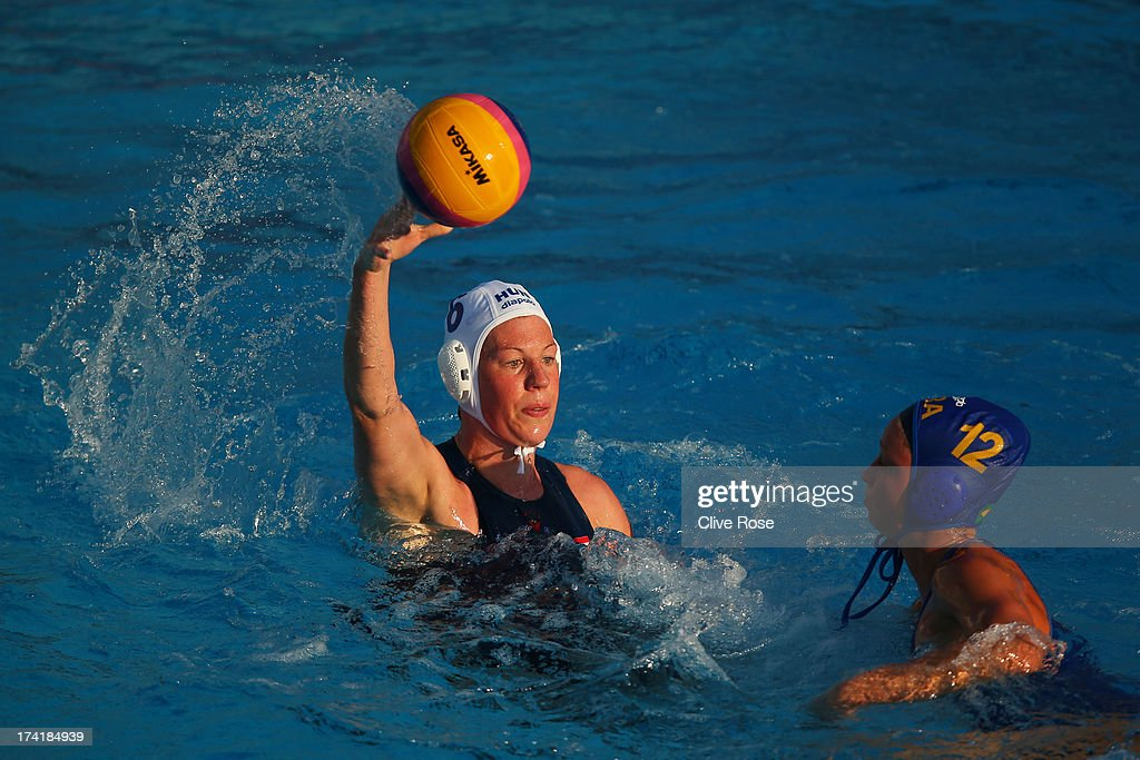 Captain Orsolya Takacs of Hungary looks to pass the ball under pressure from Viviane Bahia of Brazil during the Women's Water Polo first preliminary round match between Hungary and Brazil during Day Two of the 15th FINA World Championships at Piscines Bernat Picornell on July 21, 2013 in Barcelona, Spain.