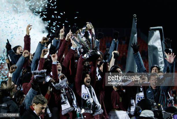Captain Pablo Mastroeni of the Colorado Rapids holds the Philip F Anschutz Trophy and celebrates with teammates after their 21 overtime victory...