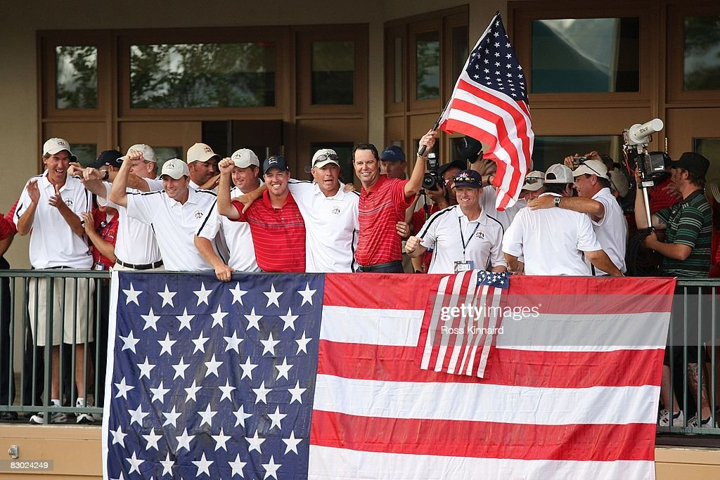 Captain Paul Azinger of the USA team holds an American flag while celebrating with players and caddies during the USA 16 1/2 11 1/2 victory on the...
