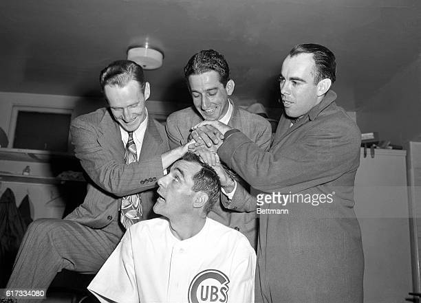 Captain Phil Cavarretta of National Champion Chicago Cubs gets his batting crown from pitcher Hank Borowy first baseman Reggie Otera and outfielder...