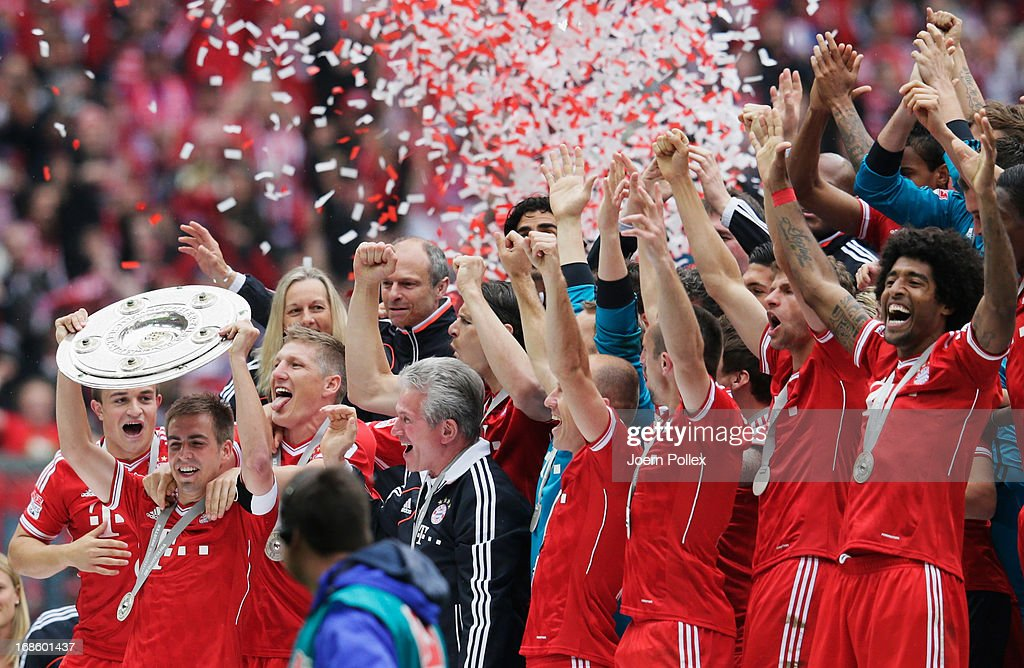 Captain <a gi-track='captionPersonalityLinkClicked' href=/galleries/search?phrase=Philipp+Lahm&family=editorial&specificpeople=483746 ng-click='$event.stopPropagation()'>Philipp Lahm</a> celebrates with FC Bayern Muenchen team mates as they receive the championship trophy after the Bundesliga match between FC Bayern Muenchen and FC Augsburg at the Allianz Arena on May 11, 2013 in Munich, Germany.