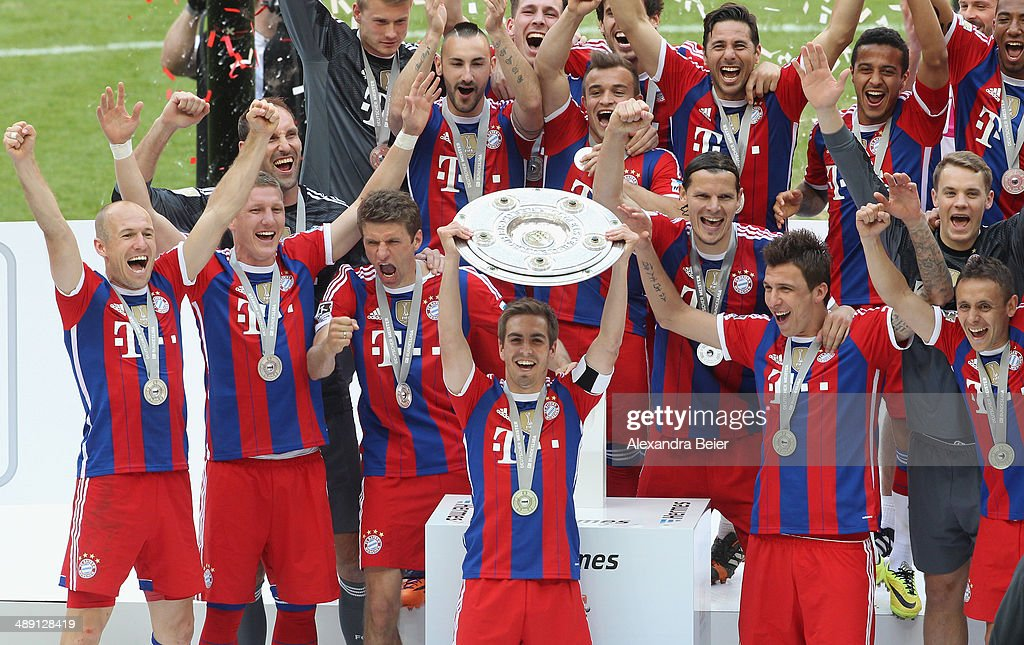 Captain Philipp Lahm of Bayern Muenchen lifts the trophy with team mates to celebrate winning the German Championship after the Bundesliga match between FC Bayern Muenchen and VfB Stuttgart at Allianz Arena on May 10, 2014 in Munich, Germany.