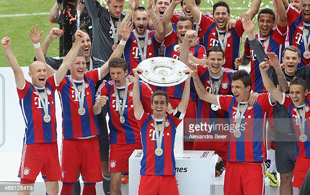 Captain Philipp Lahm of Bayern Muenchen lifts the trophy with team mates to celebrate winning the German Championship after the Bundesliga match...