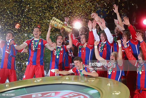 Captain Philipp Lahm of Bayern Muenchen lifts the trophy with team mates to celebrate victory after the DFB Cup Final match between Borussia Dortmund...