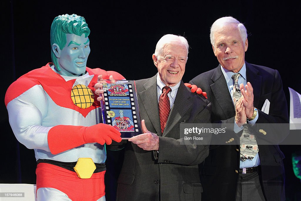 Captain Planet, Former President <a gi-track='captionPersonalityLinkClicked' href=/galleries/search?phrase=Jimmy+Carter+-+US+President&family=editorial&specificpeople=93589 ng-click='$event.stopPropagation()'>Jimmy Carter</a> and Captain Planet Co-Founder <a gi-track='captionPersonalityLinkClicked' href=/galleries/search?phrase=Ted+Turner+-+Businessman&family=editorial&specificpeople=203000 ng-click='$event.stopPropagation()'>Ted Turner</a> appear on stage during the Captain Planet Foundation's benefit gala at Georgia Aquarium on December 7, 2012 in Atlanta, Georgia. Former President <a gi-track='captionPersonalityLinkClicked' href=/galleries/search?phrase=Jimmy+Carter+-+US+President&family=editorial&specificpeople=93589 ng-click='$event.stopPropagation()'>Jimmy Carter</a> received the 2012 Captain Planet Foundation Exemplar Award during the gala.