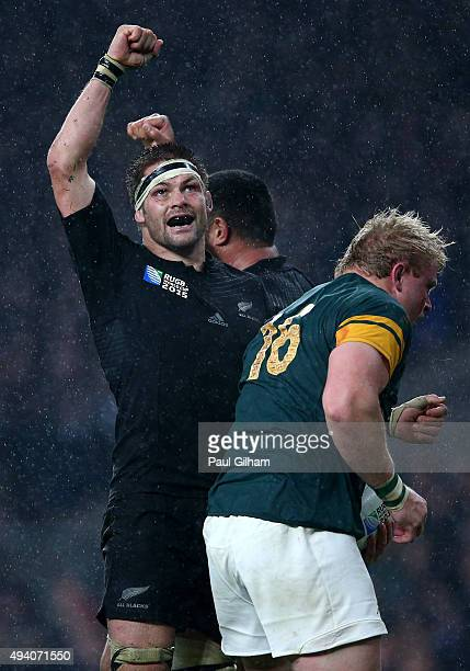 Captain Richie McCaw of the New Zealand All Blacks punches the air to celebrate victory as Adriaan Strauss of South Africa walks by during the 2015...