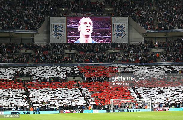 Captain Rio Ferdinand of England is seen on the TV screen as England fans show their support during the national anthem during the UEFA EURO 2012...