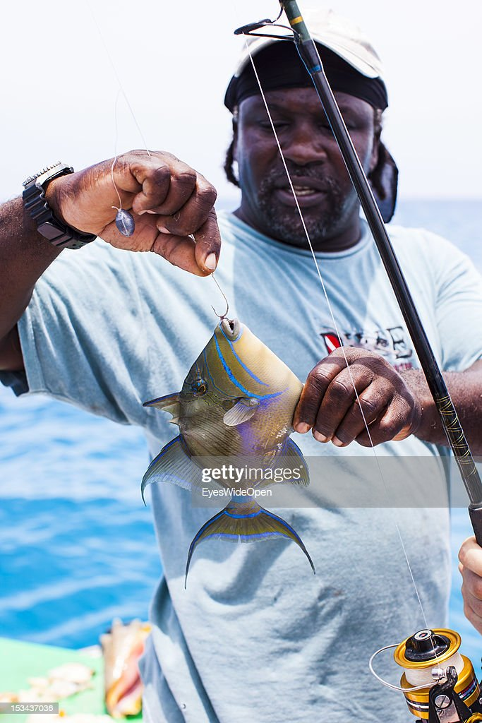 Captain Rob has catched a trigger fish on the hook from his fishing rod at his yacht on June 15, 2012 in Long Island, The Bahamas.
