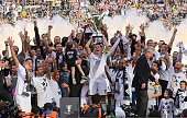 Captain Robbie Keane of the Los Angeles Galaxy stands on the podium and hoists over his head the Philip F Anschutz Trophy after the Galaxy defeated...