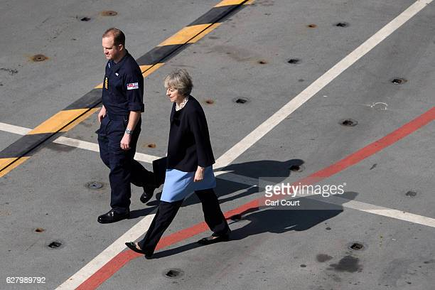 Captain Robert Pedre accompanies British Prime Minister Theresa May as she walks on the deck of the ship to address address sailors on board HMS...