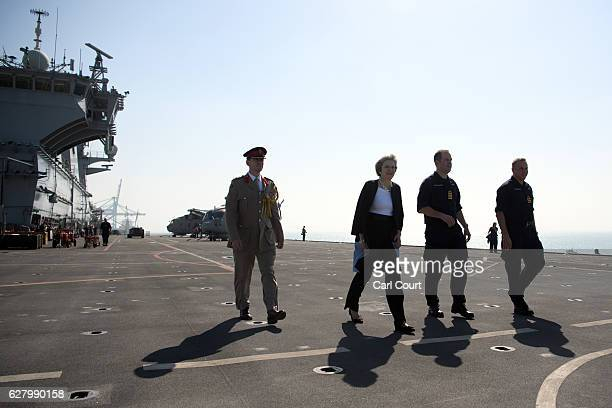 Captain Robert Pedre accompanies British Prime Minister Theresa May as she walks on the deck of the ship after addressing sailors on board HMS Ocean...