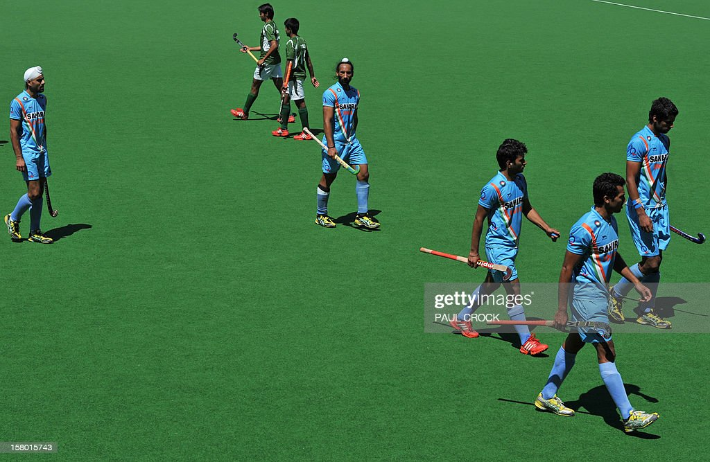 Captain Sadar Singh of India (C) and members of the team leave the pitch after losing the bronze medal match against Pakistan at the men's Hockey Champions Trophy tournament in Melbourne on December 9, 2012. IMAGE STRICTLY RESTRICTED TO EDITORIAL USE - STRICTLY NO COMMERCIAL USE. AFP PHOTO/Paul CROCK