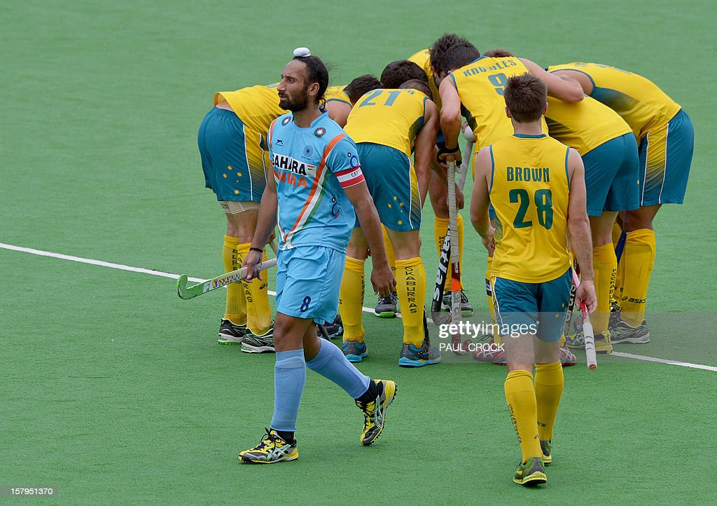 Captain Sadar Singh of India (L) walks past the Australian team as they prepare for a penalty corner during the second semifinal at the men's Hockey Champions Trophy tournament in Melbourne on December 8, 2012. IMAGE STRICTLY RESTRICTED TO EDITORIAL USE - STRICTLY NO COMMERCIAL USE AFP PHOTO / Paul CROCK