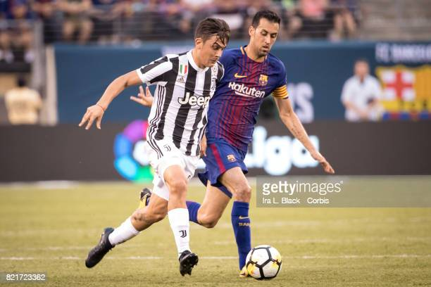 Captain Sergio Busquets of Barcelona tries to stop the advance of Paulo Dybala of Juventus during the International Champions Cup match between FC...