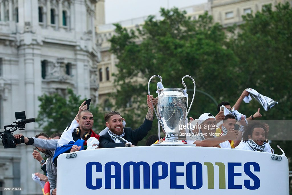 Captain Sergio Ramos (2ndL) of Real Madrid CF holds the trophy in celebration surrounded by his teammates Pepe (L), goalkeeper Keylor Navas (3dL) and Marcelo (R) as they arrive by bus to Cibeles square after winning the Uefa Champions League Final match agains Club Atletico de Madrid on May 29, 2016 in Madrid, Spain.