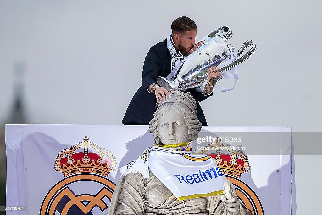 Captain Sergio Ramos of Real Madrid kisses the trophy as he touches Cibeles statue head as he celebrate with his team and fans at Cibeles square after winning the Uefa Champions League Final match against Club Atletico de Madrid on May 29, 2016 in Madrid, Spain.