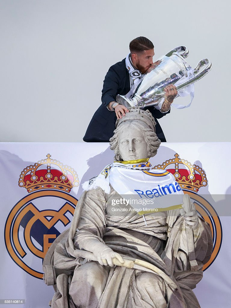 Captain Sergio Ramos of Real Madrid kisses the Trophy as he touches Cibeles font head as he celebrate with his team and fans at Cibeles square after winning the Uefa Champions League Final match against Club Atletico de Madrid on May 29, 2016 in Madrid, Spain.