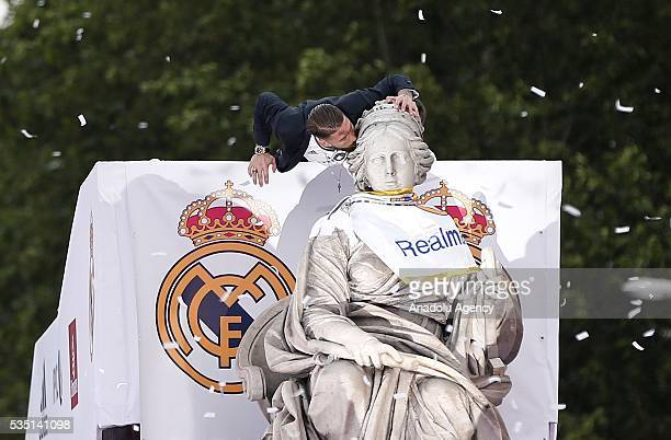 Captain Sergio Ramos of Real Madrid places a Real Madrid scarf at Cibeles statue during their team celebration at Cibeles Square after winning the...