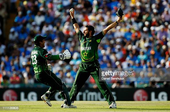 Captain Shahid Afridi of Pakistan celebrates with team mate Kamran Akmal after taking the catch to dismiss Sachin Tendulkar of India off the bowling...