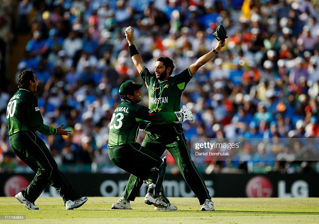 Captain <a gi-track='captionPersonalityLinkClicked' href=/galleries/search?phrase=Shahid+Afridi&family=editorial&specificpeople=193846 ng-click='$event.stopPropagation()'>Shahid Afridi</a> of Pakistan celebrates with team mates <a gi-track='captionPersonalityLinkClicked' href=/galleries/search?phrase=Kamran+Akmal&family=editorial&specificpeople=221679 ng-click='$event.stopPropagation()'>Kamran Akmal</a> and <a gi-track='captionPersonalityLinkClicked' href=/galleries/search?phrase=Saeed+Ajmal&family=editorial&specificpeople=2247219 ng-click='$event.stopPropagation()'>Saeed Ajmal</a> after taking the catch to dismiss Sachin Tendulkar of India off the bowling of <a gi-track='captionPersonalityLinkClicked' href=/galleries/search?phrase=Saeed+Ajmal&family=editorial&specificpeople=2247219 ng-click='$event.stopPropagation()'>Saeed Ajmal</a> of Pakistan during the 2011 ICC World Cup second Semi-Final between India and Pakistan at Punjab Cricket Association (PCA) Stadium on March 30, 2011 in Mohali, India.